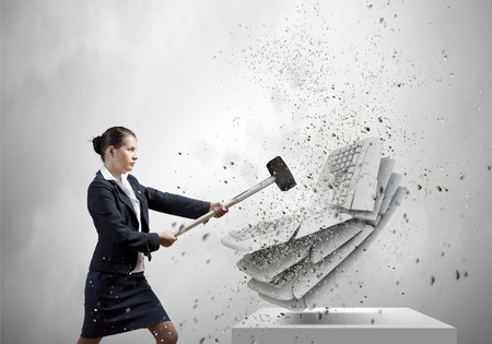 Businesswoman in anger crashing keyboard with hammer photo