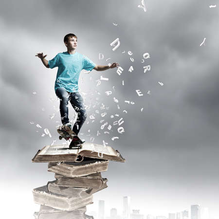 Boy skater standing on pile of old books photo