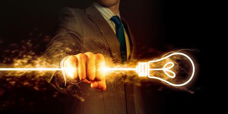 Homme d'affaires tenant la foudre en puissance et contrôle poing Banque d'images