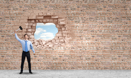 determined: Young determined businessman breaking wall with hammer Stock Photo