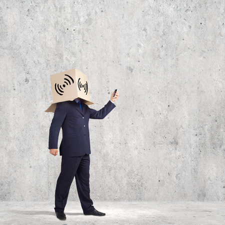 unknown gender: Businessman using mobile phone wearing carton box on head