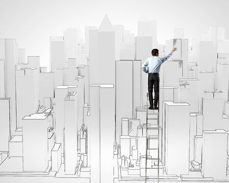 Back view of businessman standing on ladder and drawing buildings photo