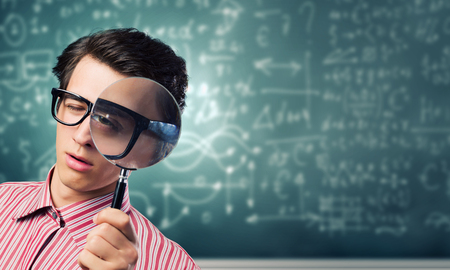 obsessed: Young man scientist looking in magnifying glass