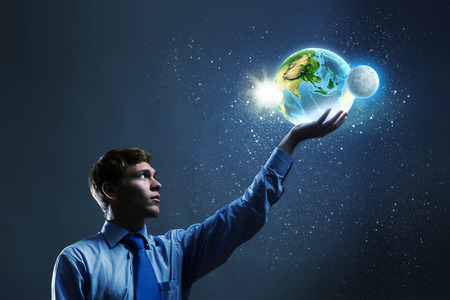 Young businessman holding Earth planet in palm  Elements of this image are furnished by NASA photo