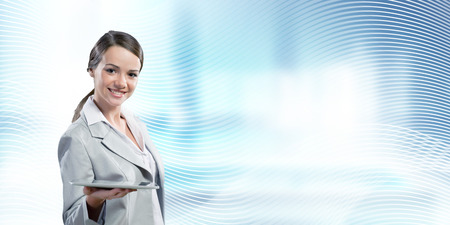 advertisment: Attractive smiling businesswoman holding tablet pc in hands