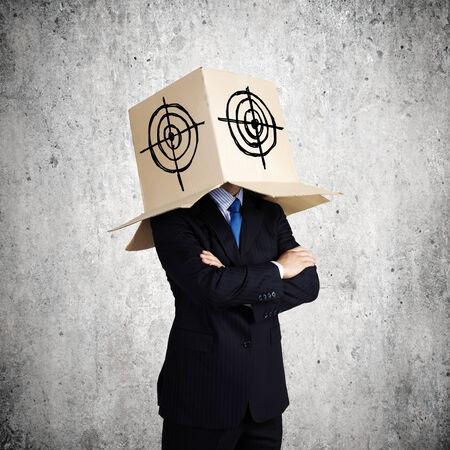 Man wearing carton box with target on head