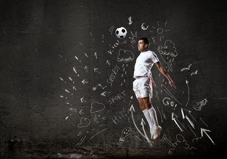 Football player in jump striking ball with sketches at backdrop photo
