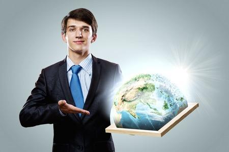 protecting your business: Apuesto hombre de negocios bastidor de sujeci�n con el planeta Tierra