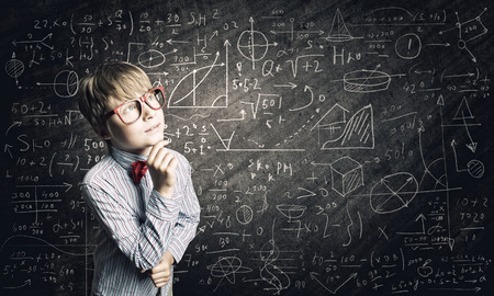 Genius boy in red glasses near blackboard with formulas photo