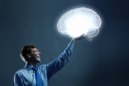 Young man holding human brain in hand photo