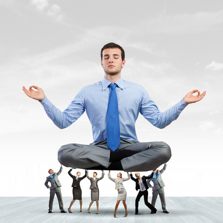 supported: Young businessman sitting in lotus pose and supported by colleagues