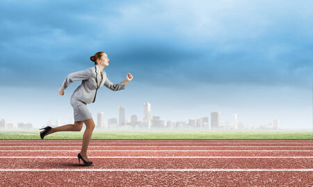 Young businesswoman in suit running on track Stock Photo
