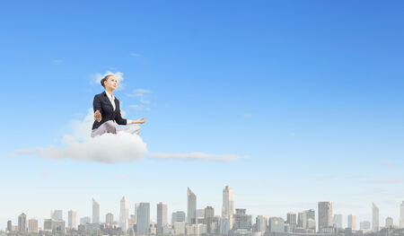 Young attractive woman sitting on cloud and meditating photo