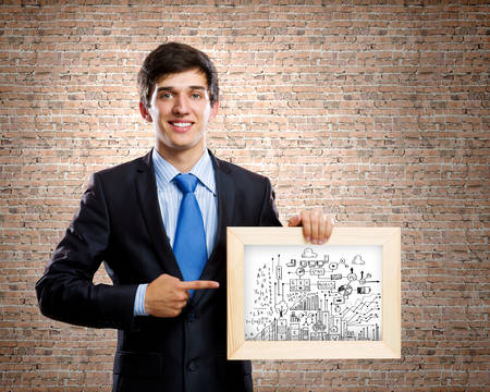 Handsome businessman holding frame with business sketches photo
