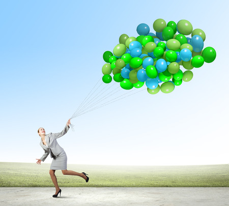 Young businesswoman running with bunch of colorful balloons photo