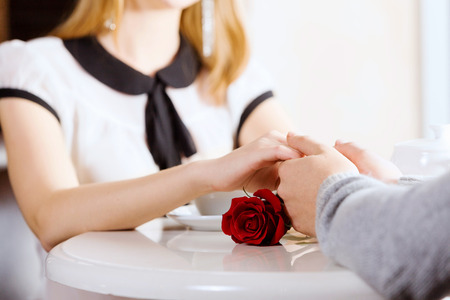 Close up image of young couple holding hands having date at cafe photo