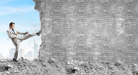 karate kick: Businessman breaking stone wall with karate kick