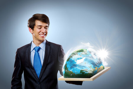 Handsome businessman holding frame with Earth planet  Elements of this image are furnished by NASA photo