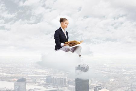Jonge aantrekkelijke zakenvrouw zit op wolk en lezen boek Stockfoto