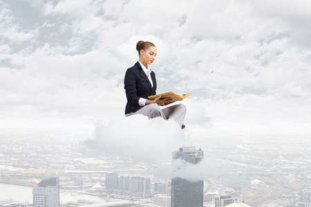 Young attractive businesswoman sitting on cloud and reading book
