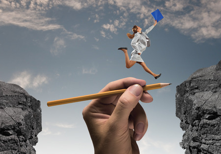 Young businesswoman jumping over gap  Risk concept