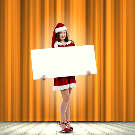 Girl in Santa costume with white blank banner  Place for text photo