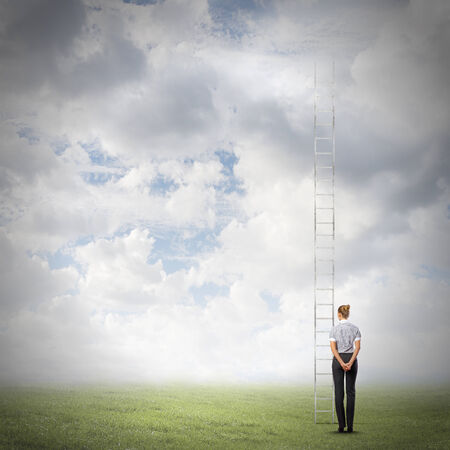 goal oriented: Rear view of businesswoman standing near ladder going high in sky Stock Photo