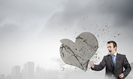 Young businessman breaking stone heart with punch photo