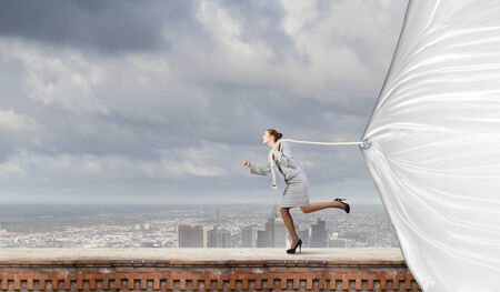 commercialism: Young businesswoman running and pulling white blank banner