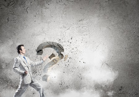 Businessman breaking stone question mark with karate kick Stock Photo