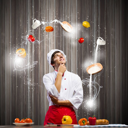Young thoughtful cook and ingredients flying in air photo