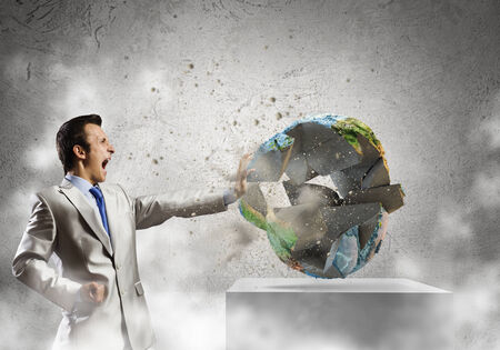 Young determined businessman crashing Earth planet with punch  photo