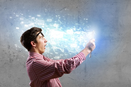 Young man looking shocked in tablet pc Stock Photo