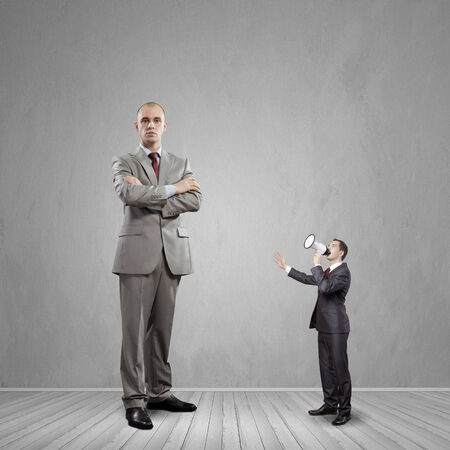 bossy: Big bossy businessman looking down at small businessman Stock Photo