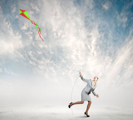 Young happy businesswoman running with colorful kite photo