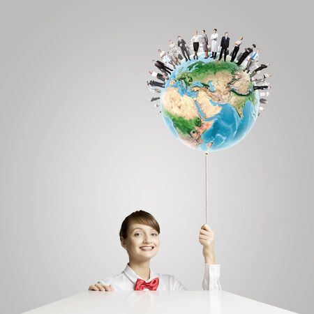 Young smiling woman holding balloon colored like Earth planet  Elements of this image are furnished by NASA Stock Photo