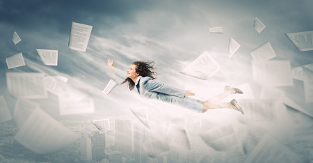 Young determined businesswoman flying high in sky photo