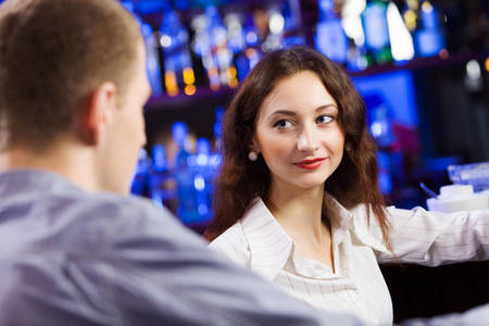Young couple in bar having drinks and talking Stock Photo
