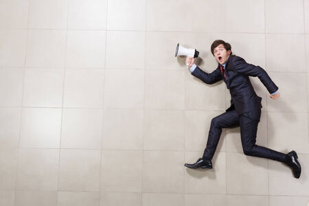 Funny image of running businessman holding megaphone