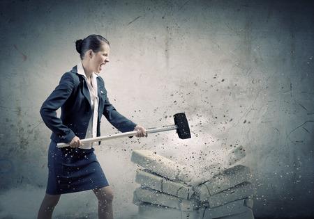 Jonge boos zakenvrouw crashen bakstenen met hamer