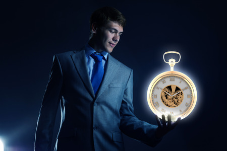 Young businessman holding pocket watch in hand photo