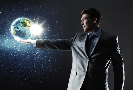 Young businessman holding Earth planet in hand   photo