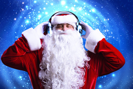 Santa Claus wearing headphones and enjoying music photo
