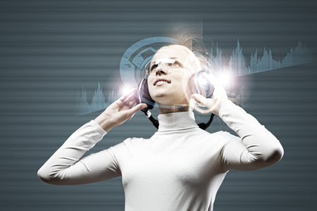 Young woman in white wearing headphones against media background photo