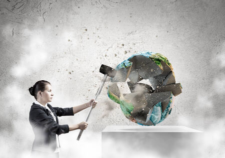 Businesswoman in anger crashing earth planet with hammer  Elements of this image are furnished by NASA photo