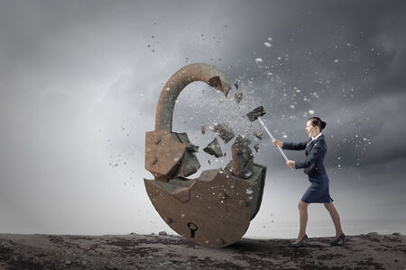 Young angry businesswoman crashing stone lock with hammer photo