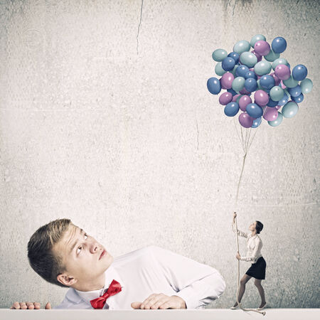Businessman looking at woman holding bunch of colorful balloons photo