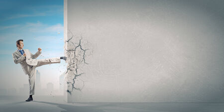 frenzy: Businessman breaking stone wall with karate kick