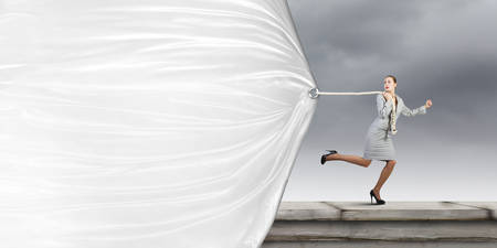 Young businesswoman running and pulling white blank banner photo
