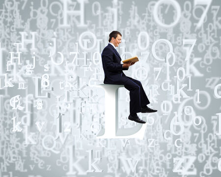 Young businessman sitting on letter and reading book photo